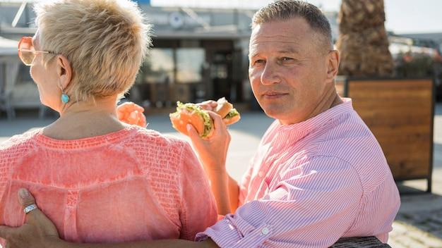 素敵なハンバーガーを楽しんでいるビーチで老夫婦