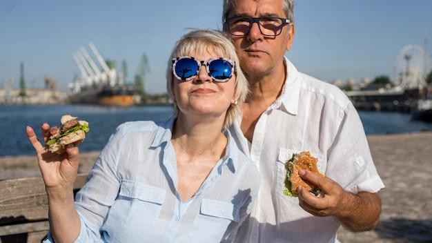 屋外で一緒にハンバーガーを楽しんでいる老夫婦
