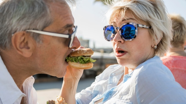 屋外でハンバーガーを楽しんでいる老夫婦