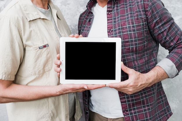 Elder couple holding a tablet