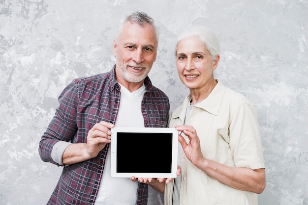 Elder couple holding a tablet