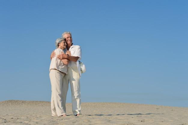 砂の中を裸足で歩く恋の老夫婦