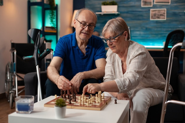 Elder couple playing chessboard game on table