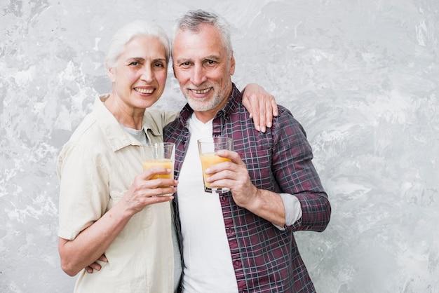 Elder couple posing with juice