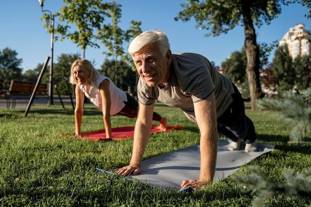 야외에서 요가 연습하는 노인 부부