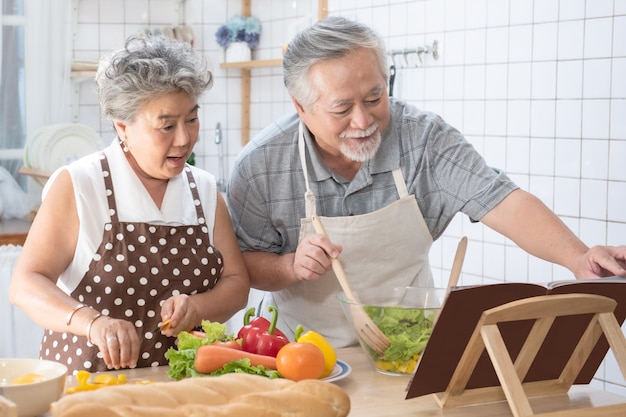 Elder couple read cookbook cooking in kitchen