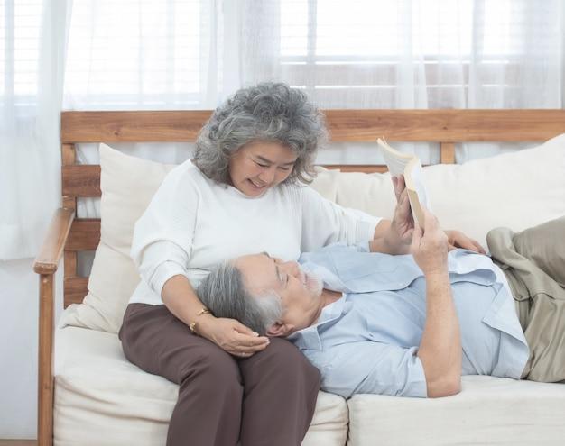 노인 부부는 집에서 소파 읽기 책에 앉아