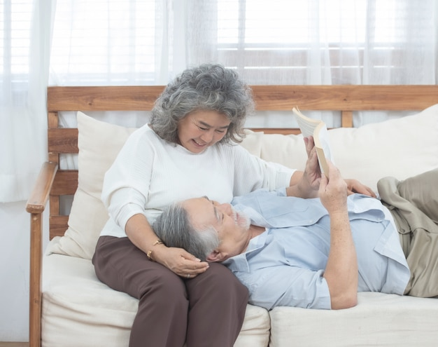Пожилая пара сидит на диване и читает книгу дома