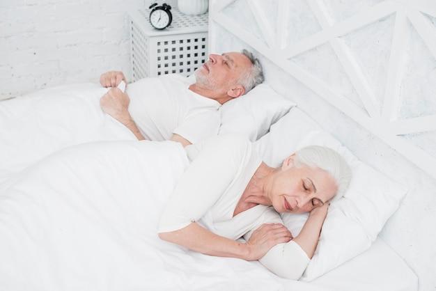 白いベッドで寝ている年配のカップル