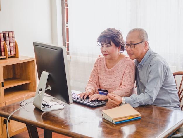 高齢者のカップルが自宅でコンピューターとクレジットカードを使用して