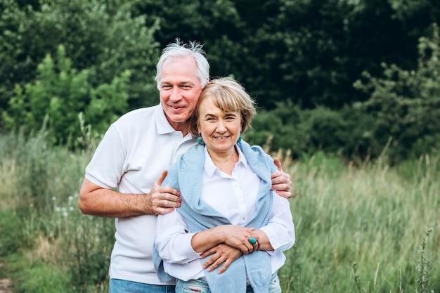 Пожилая пара гуляет на природе и обнимается
