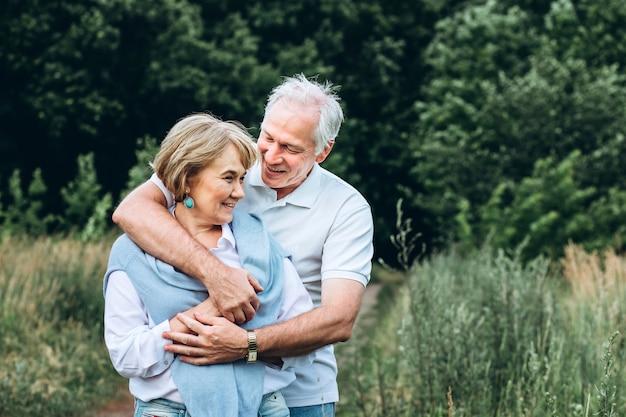 老夫婦は自然の中を歩き、抱擁