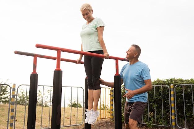 公園で一緒に運動する老夫婦
