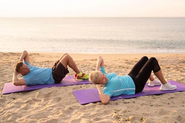 ビーチで一緒に運動する老夫婦