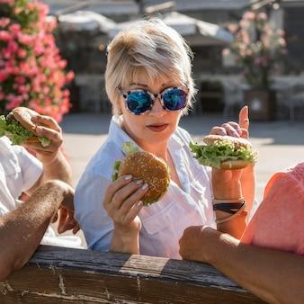 ハンバーガーを一緒に楽しんでビーチで老夫婦