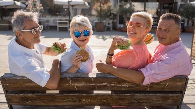 Coppie anziane in spiaggia che mangiano hamburger insieme