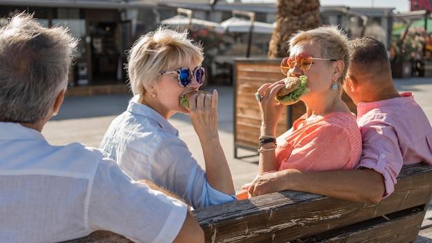 ビーチでハンバーガーを一緒に食べる老夫婦