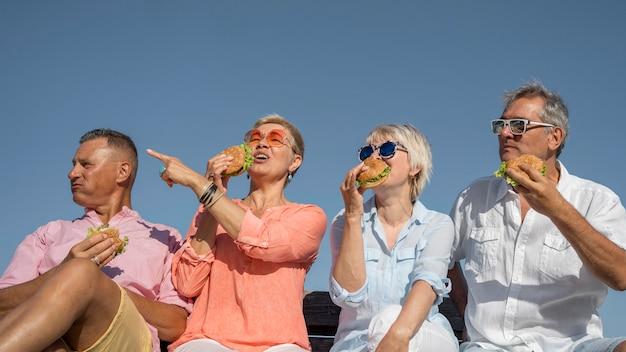 ハンバーガーを食べてビーチで一緒に高齢者のカップル