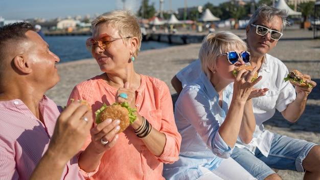 ハンバーガーを楽しんでいるビーチで一緒に高齢者のカップル