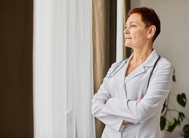 Medico femminile del centro di recupero covid anziano che osserva attraverso la finestra con lo spazio della copia