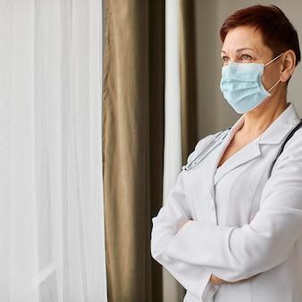 Medico femminile del centro di recupero covid anziano con mascherina medica guardando attraverso la finestra