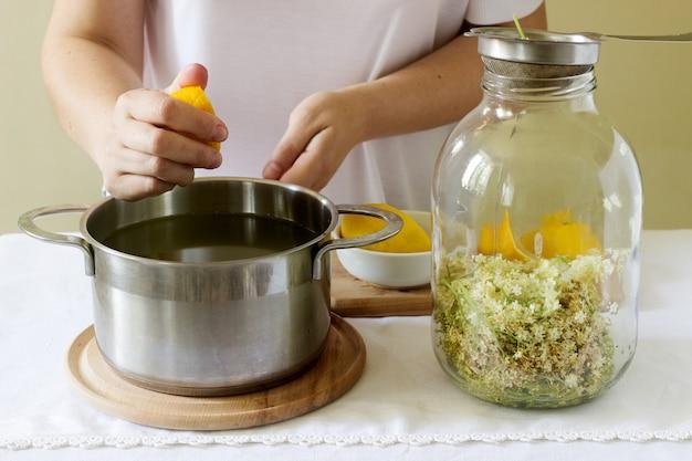 ニワトコの花、水、レモン、砂糖、食材、ニワトコシロップを準備する女性。素朴なスタイル。
