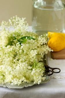 高齢者の花、水、レモン、砂糖、高齢者シロップを作るための成分。素朴なスタイル。