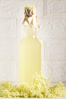ヘルダーで爽やかな夏の飲み物。ニワトコの花の瓶の中の自家製ニワトコの花のシロップのクローズアップ。夏の飲み物エルダーフラワーシロップ、ミント、ライム入りのヒューゴシャンパンドリンク。