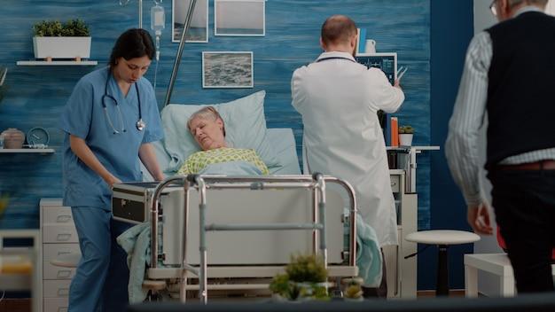 Пожилой мужчина просит помощи у врача и медсестры