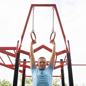 Пожилой мужчина тренируется на открытом воздухе