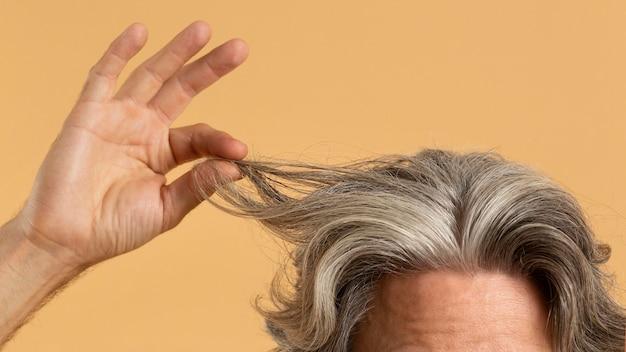 Uomo anziano che tiene i suoi capelli grigi