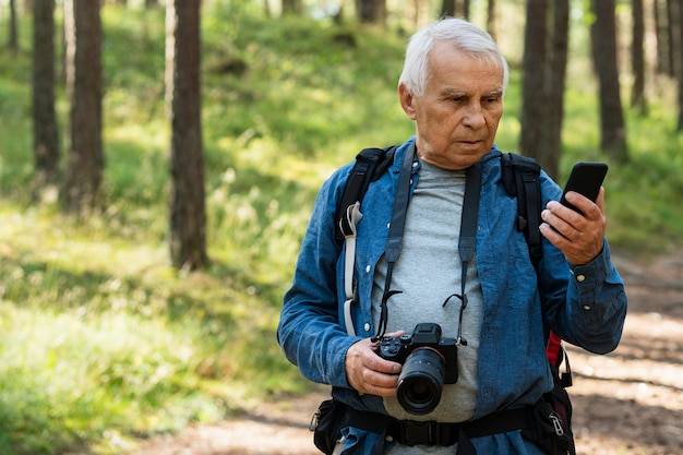 Elder man looking at smartphone while backpacking in nature