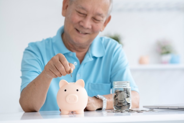 투자 및 은퇴 저축 기획 저축으로 돼지 저금통 안에 동전을 넣어 웃 고 노인 남자.