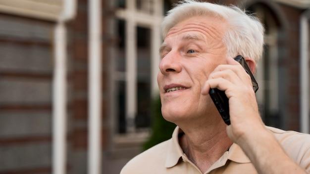 Пожилой мужчина берет смартфон в городе