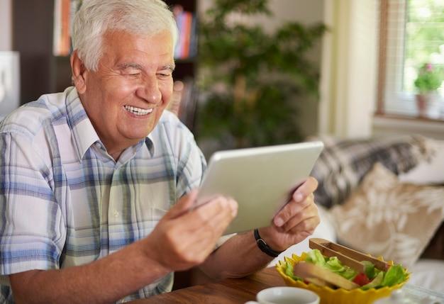 테이블에서 디지털 태블릿을 사용하는 노인