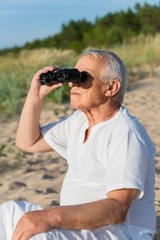 Elder man using binoculars at the beach to explore nature