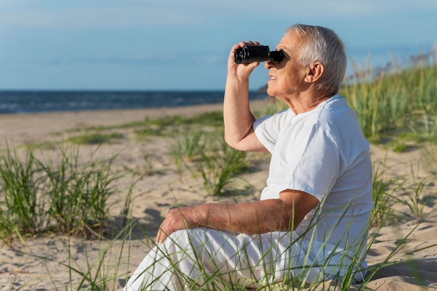 해변에서 휴식하는 동안 쌍안경을 사용하는 노인