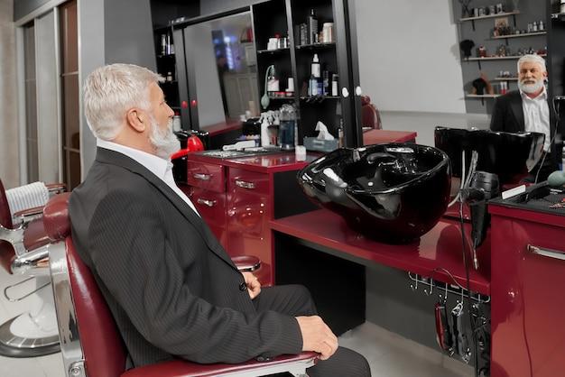 Пожилой мужчина в черном нарядном костюме сидит в парикмахерской