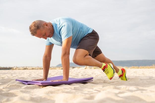 Пожилой мужчина работает на пляже