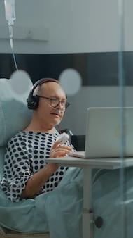 Elder patient using laptop and headphones in hospital ward