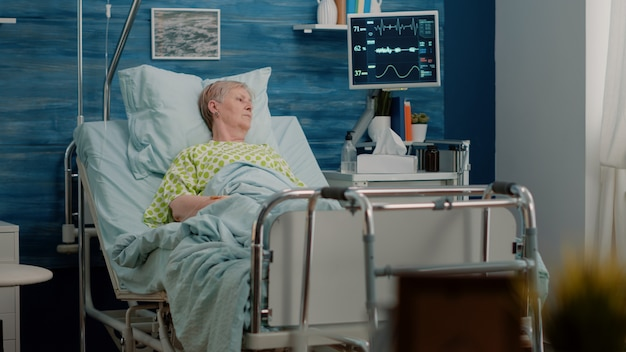 Elder patient with sickness laying in hospital bed