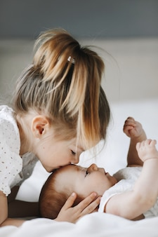 Elder sister is kissing little baby girl in the forehead with closed eyes
