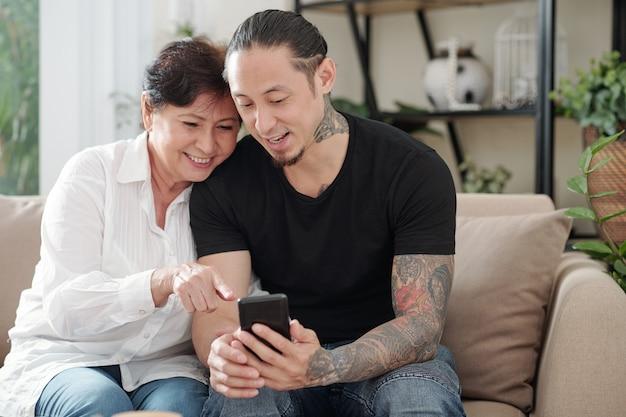 自宅のソファで休んでいる幸せな母親に携帯電話で写真を見せている長男