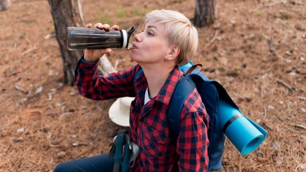 高齢者のツーリストの女性が水分補給のために水を飲む