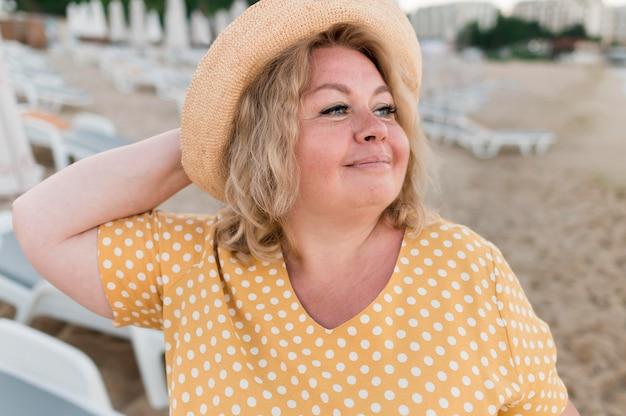 Старшая туристическая женщина позирует на пляже