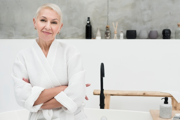 Elder woman in bathrobe posing with arms crossed