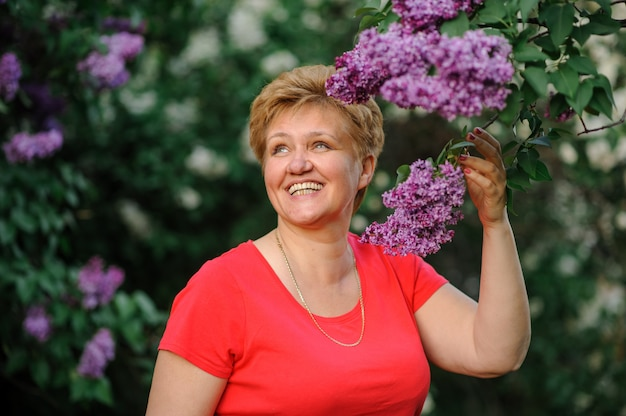 Elder woman in casual wear posing near a flowering lilac.