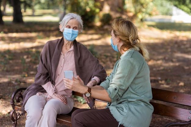 Пожилая женщина разговаривает с женщиной на скамейке на открытом воздухе, держа в руке смартфон