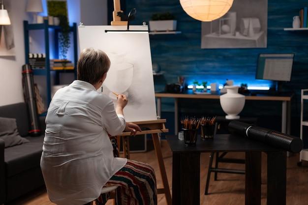 Пожилая женщина рисует дизайн вазы со стола на холсте