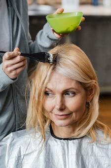 自宅で美容師に髪を染めてもらう年配の女性